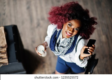 Attractive african american curly girl in white blouse and blue shorts posed at cafe with latte and mobile phone at hand. View from above.