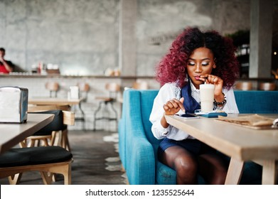 Attractive african american curly girl sitting at cafe drinking latte and looking at mobile phone.