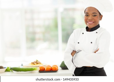 attractive african american female chef with arms folded in restaurant kitchen