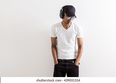Attractive african american guy in cap and sunglasses listening to music with headphones on light background