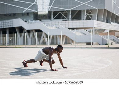 Attractive African American man does burpees working out on the street
