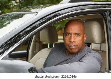 Attractive African American man sitting in a car looking at the camera.