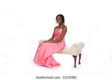 Attractive African American teenage girl wearing a pink strapless gown, sitting on an ivory bench against a white background.