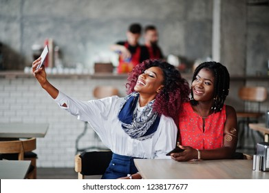 Attractive african american two girls friends sitting at table on cafe making selfie on phone.