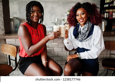 Attractive african american two girls friends sitting at chairs against bar on pub and drinking latte.