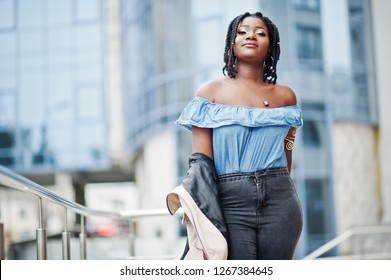 Attractive african american woman with dreads in jacket posed near railings against modern multistory building.