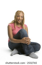 Attractive African American woman in jeans sitting on the floor