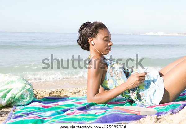 Attractive african american woman on the beach, listening to music with her mp4 player while relaxing on a towel on vacation.
