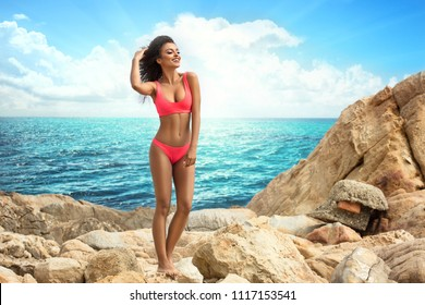 Attractive african american woman with perfect fit body relaxing on the rocky beach, wearing pink fashionable swimsuit. Sunny summer vacation day.