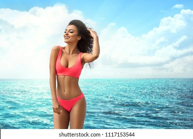 Attractive african american woman with perfect fit body relaxing on the beach, wearing pink fashionable swimsuit. Sunny summer vacation day.