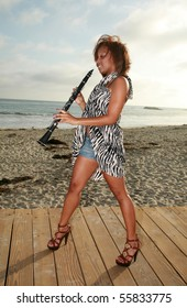 an attractive african american woman plays her clarinet outside at the beach for all to hear and enjoy