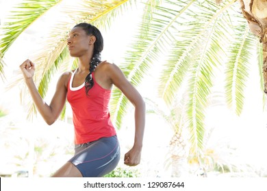 Attractive african american woman running in the city under a palm tree, training for fitness.