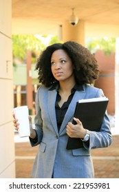 Attractive African AmericanBusiness Professional BusinessWoman with Black Hair Drinking Coffee Holding Folder