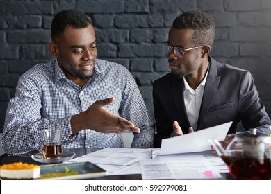 Attractive African businessman in glasses and suit holding papers, showing presentation of his project to cheerful business partner, who smiling happily, supporting his idea with positive gesture