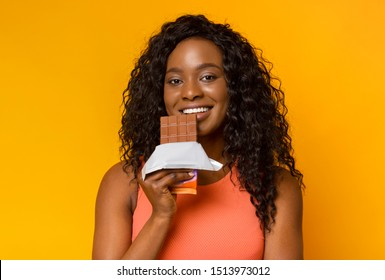 Attractive african girl holding milk chocolate next to her lips and smiling, yellow background
