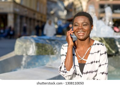 Attractive African woman chatting on her mobile phone in front of an urban water feature smiling with pleasure as she listens to the conversation
