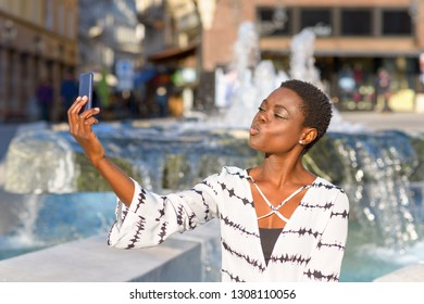 Attractive African woman posing for a selfie on her mobile phone in a city street pouting her lips at the camera