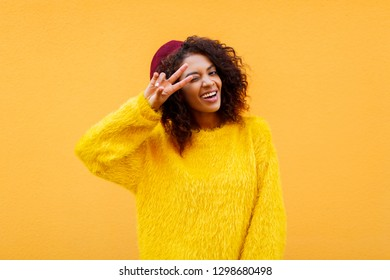 Attractive  African woman with wavy hairs  over yellow urban wall.  Perfect teeth.  Stylish black girl shows signs by hand.