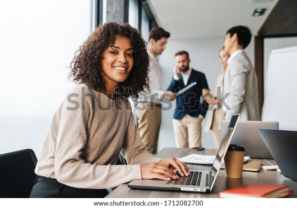 Attractive african young confident businesswoman sitting at the office table with group of colleagues in the background, working on laptop computer