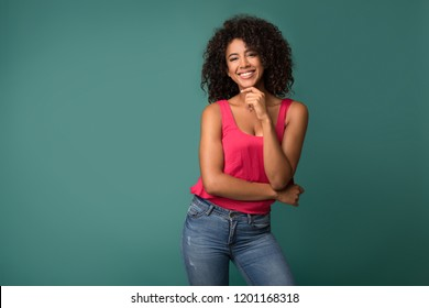 Attractive african-american model posing against turquoise background