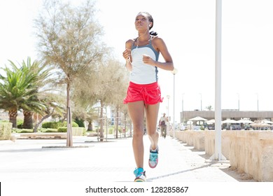 Attractive african-american woman running and exercising in the city, listening to music with her ear phones on a sunny day.