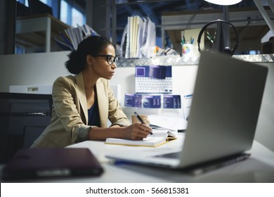 Attractive afro american business coach preparing information for training lesson with students searching interesting information on internet while using modern computer and wireless connection