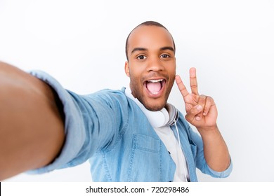Attractive afro american emigrant stylish teen is doing photoshot for his blog, on pure white backgound, astonished, carefree, wearing denim shirt, with wide open mouth, showing peace gesture