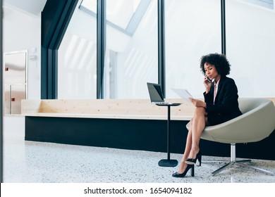 魅力的なアフロアメリカ人女性起業家コンサルタントで、携帯電話で会社の会計報告に関するアシスタント、スタイリッシュな正装の黒人女性が企業戦略に関する話をします