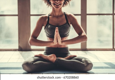 Attractive Afro American girl in sportswear is doing yoga and smiling