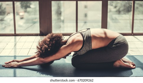 Attractive Afro American girl in sportswear is doing yoga