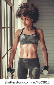 Attractive Afro American girl in sportswear is working out with dumbbells