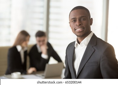 Attractive afro american smiling businessman looking at camera standing in foreground, young cheerful african leading manager posing with subordinates at the background, multi-ethnic team portrait