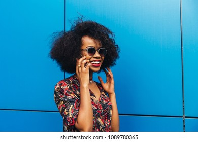 Attractive afro american woman, smiling cheerfully while having mobile conversation. Dressed in colorful blouse, in sunglasses, with short lush hair. Outdoors.