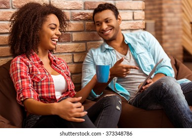 Attractive Afro-American couple using tablet, holding a cup and laughing while sitting on beanbag chairs against brick wall