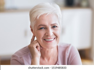 Attractive aged business lady smiling at camera at home, touching her ear, flirting