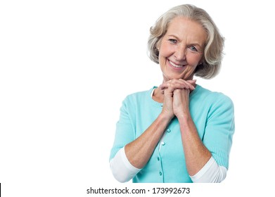 Attractive aged lady posing with clasped hands