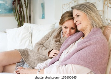 Attractive and alike adult daughter and mature mother relaxing together and being affectionate with each other while sitting on a white sofa at home and smiling, interior.