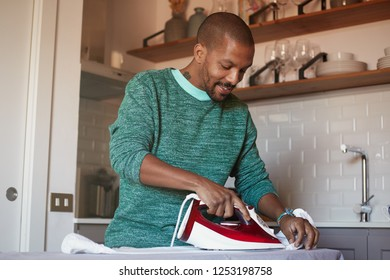 Attractive american black man is ironing white shirt at home.