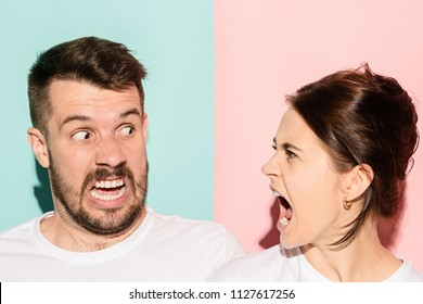 The attractive angry couple fighting and shouting at each other. quarrel concept. The studio shot on trendy pink and blue background. Human emotions concept