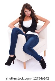 Attractive angry woman sitting in armchair, studio shot