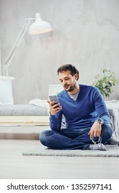 Attractive arab man dressed casual sitting on the floor in bedroom and using smart phone for reading or sending message.
