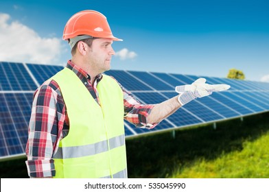 Attractive architect near solar panels showing something in his palm with copy space