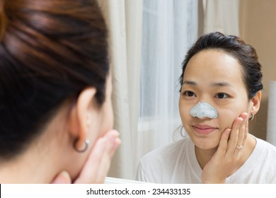 attractive asian beautiful woman caring her skin face front of mirror