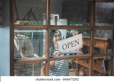 attractive asian business woman turning the open sign of her shop