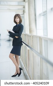 Attractive asian business woman working on tablet computer outside Office