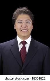 Attractive asian businessman in a suit over a black background