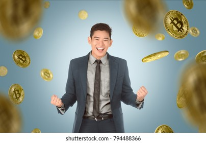 Attractive asian businessman with suit standing under bitcoin rain on blue background