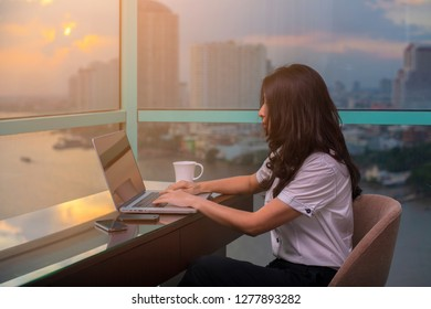 Attractive asian businesswoman typing email on laptop computer with smartphone while sitting at home and Business buildings, River on background.