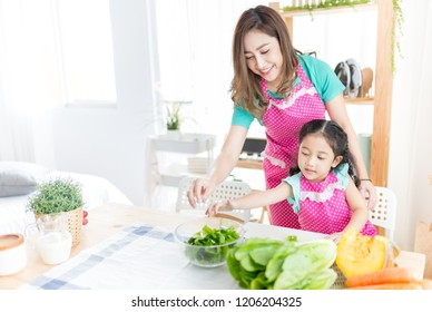 attractive asian children and her mother cooking organic vegetables salad, they show thumps up sign with hand, family time
