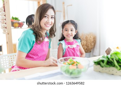 attractive asian children and her mother cooking organic vegetables salad, they  holding vegetables with hand, family time